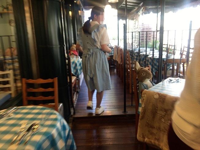テラスの空席に案内をしてくれるピーターラビットカフェの女性店員