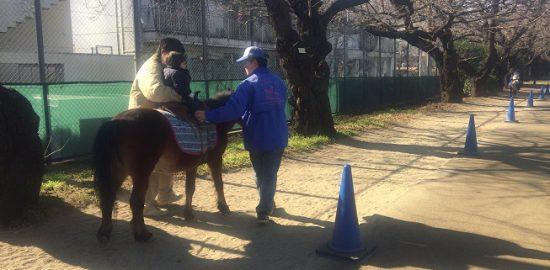 碑文谷公園でポニーに乗る子供と脇を支えるお父さん