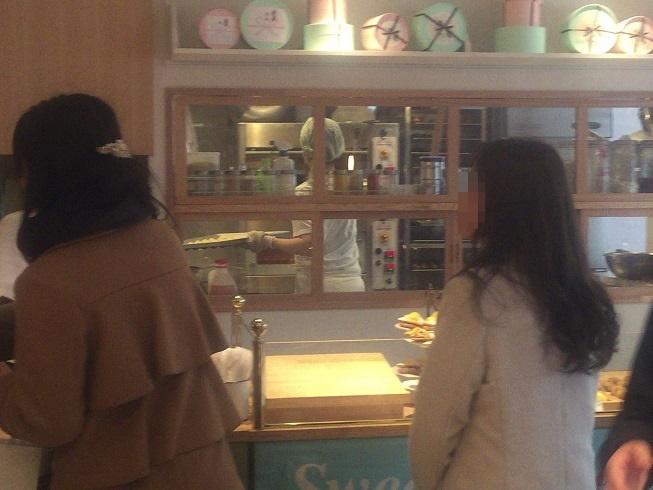 お店のカウンター奥でマドレーヌを焼く従業員