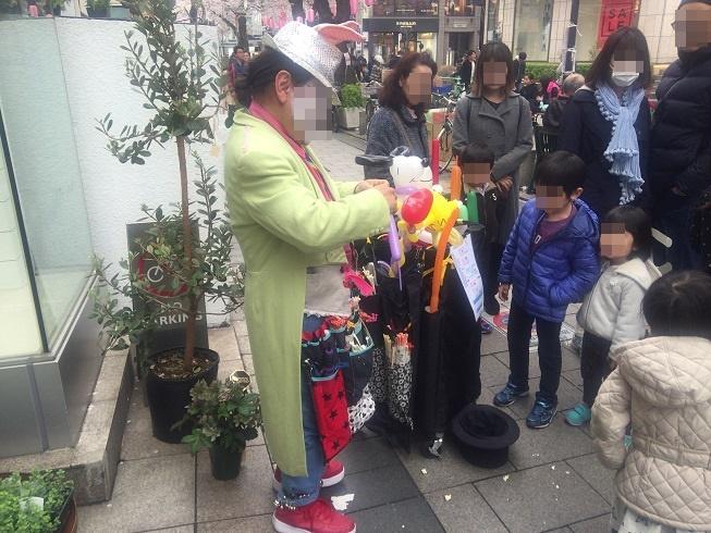 風船アートで子供達に大人気のおじさんと、風船完成を待つ家族