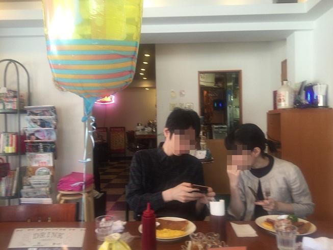 お店の中央にあるテーブル席でパンケーキを楽しむカップル