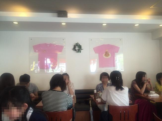 壁に掛かったパンケーキがイラストされたピンクのユニフォーム