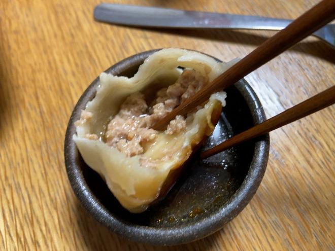 一口かじった焼き小籠包から肉汁があふれ出た画像