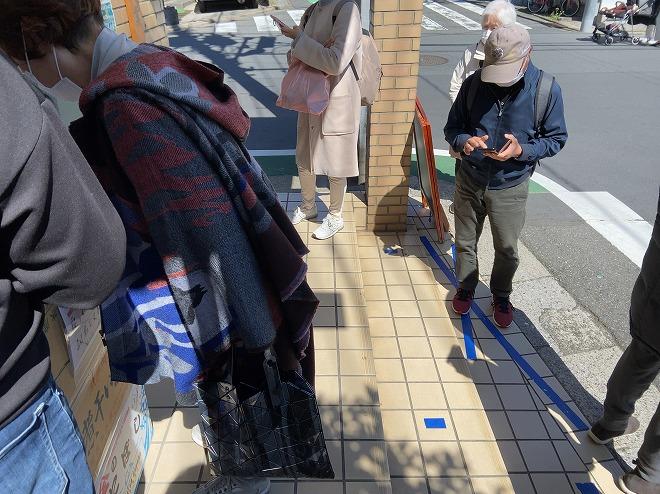 自由が丘のラーメン堀川店前で記入紙に名前を書くおばあさん